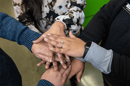 A diverse group of people stack hands in the Oportun community, excited to work together to bring better installment loan options to more people.
