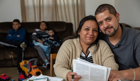 Oportun customers at their kitchen table reading their personal loan documents.
